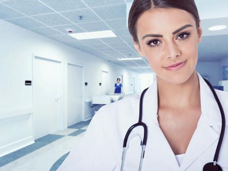 bata blanca: Retrato de mujer médico en el pasillo del hospital, mirando a cámara, sonriendo.