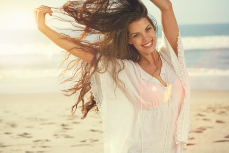 ocean background: Portrait of the beautiful girl close-up, the wind fluttering hair.
