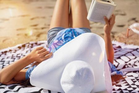 persona leyendo: Mujer en la playa leyendo un libro con una cabaña