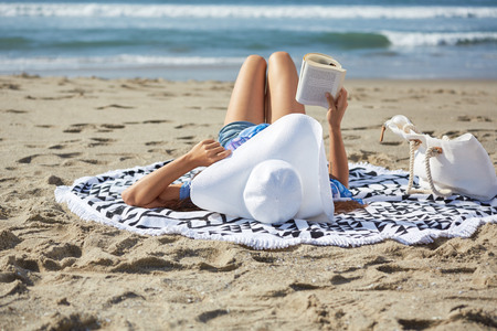 woman at the beach reading a book with a hut Foto de archivo