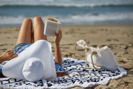 person reading: woman at the beach reading a book with a hut Stock Photo