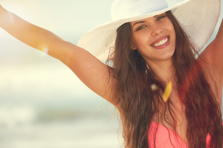 white hat: Close-up Of Beautiful Young Woman At Beach Wearing Hat