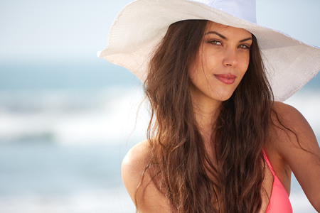 sombrero: Primer plano de la hermosa joven en la playa que desgasta el sombrero