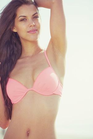 hot bikini: portrait of happy sexy girl in pink bikini posing against sea