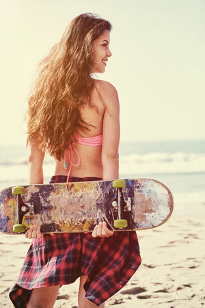 skate board: Beautiful hipster girl with skate board at the beach