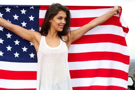 mujer que sostiene la bandera de EE.UU. al aire libre, día de la independencia, 4to de julio