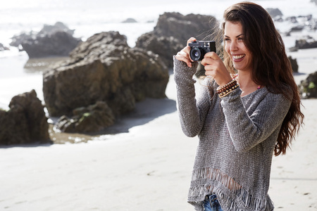 camera girl: Hipster woman taking photos with retro film camera at the beach Stock Photo