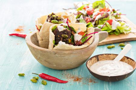Frischer Salat mit Frikadellen in Brot. Auf blauem Hintergrund
