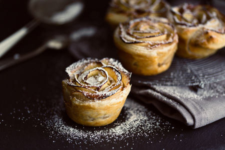 puff pastry: mini apple roses puff pastry on a dark background.