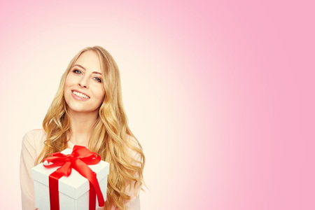 girl looking up: Young woman happy smile hold gift box in hands, isolated over pink.