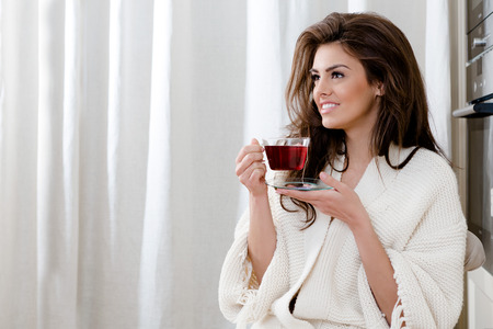 red bathrobe: beautiful thoughtful young woman drinking tea at home in the morning Stock Photo