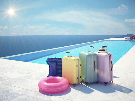 zipped: colorful suitcase and white hat next to the swimming pool