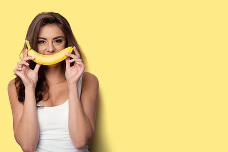 여자는 바나나와 재미를 만들기. 노란색 배경