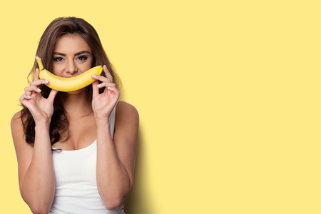 vrouw het maken van plezier met een banaan. gele achtergrond