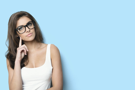 woman  glasses: thinking woman with nerd glasses. blue background Stock Photo