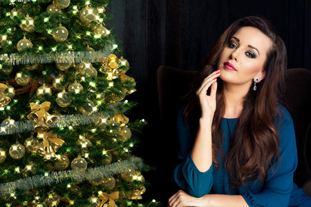 jewel: people, holidays and glamour concept - smiling woman in evening dress over christmas tree lights background