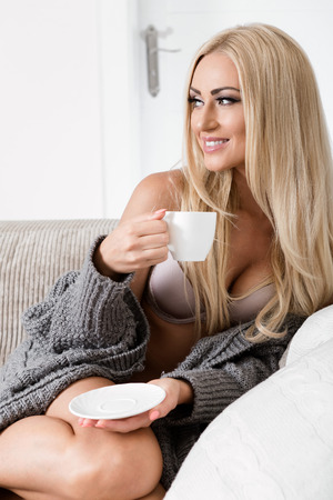 sweater girl: young woman sitting on couch with a mug.