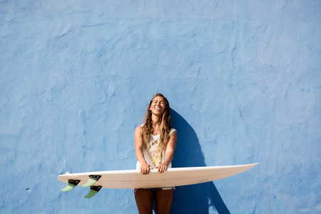 blue wall: surfer girl with surfboard in front of blue wall