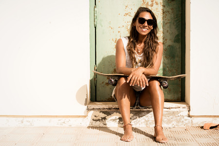 young woman smiling: young girl sitting with a skateboard in front of grunge door.
