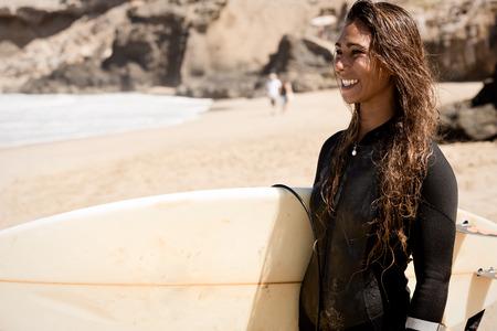 brunett: Girl standing on the beach holding a surfboard. water sport