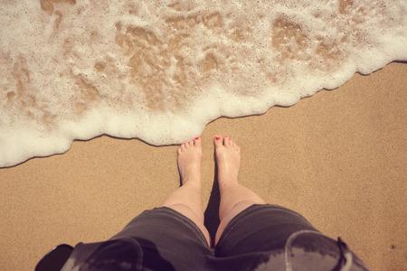 uñas pintadas: Piernas femeninas en la playa. vista superior Foto de archivo