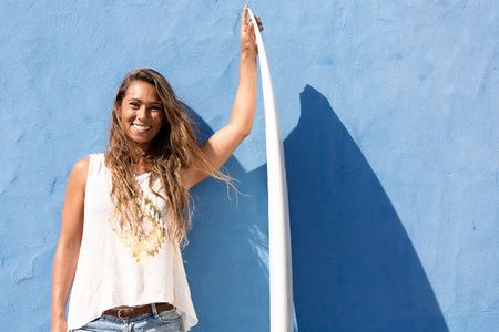 brunett: happy surfer girl with surfboard in front of blue wall