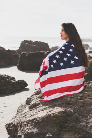 Frau in der amerikanischen Flagge eingewickelt auf Felsen sitzt auf dem besch Standard-Bild - 74238702