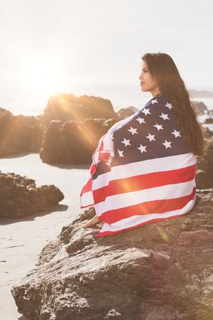 Frau in der amerikanischen Flagge eingewickelt auf Felsen sitzt auf dem besch Standard-Bild - 74303339