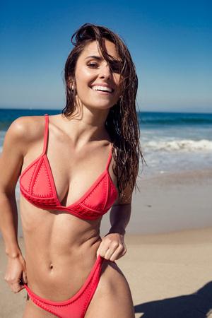 jonge vrouw die lacht op het strand.