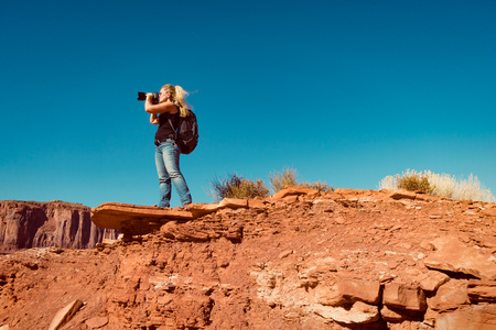 woman taking landscape photos in Arizona standing on a rock.