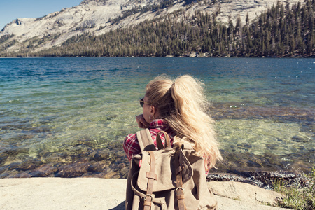 Woman sitting at a lake in Yosemite Park. Wanderlust concept