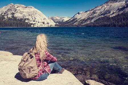 ヨセミテ公園内の湖で座っている女性。ワンダー ラストの概念 写真素材