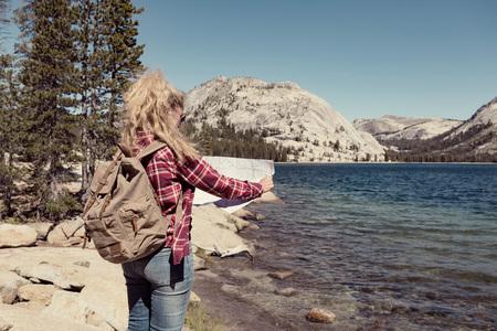 ヨセミテ公園の湖に地図を持つ女性。採り入れコンセプト 写真素材