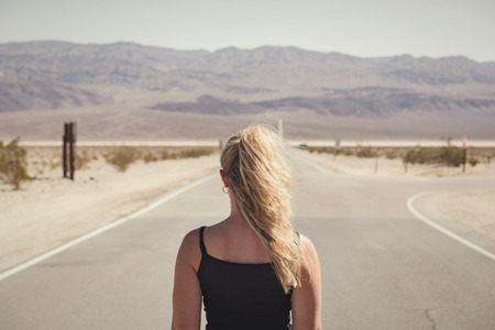woman standing alone on street in the middle of nowhere. wanderlust concept Stock Photo