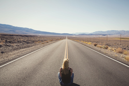 woman sitting alone on street in the middle of nowhere. wanderlust concept Stock Photo