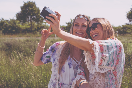 Twin sisters making a selfie with retro camera