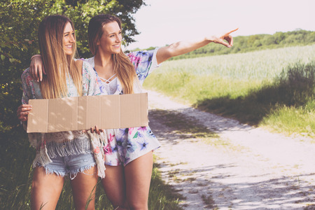 two girl friends waiting with a paper plate to hitchhiking