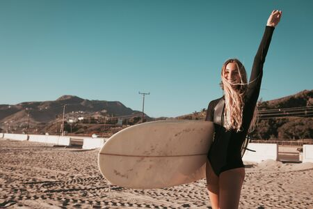 young woman standing with surfboard at Malibu beach. california lifestyle Stock Photo