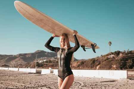 young woman standing with surfboard at Malibu beach. california lifestyle 스톡 콘텐츠