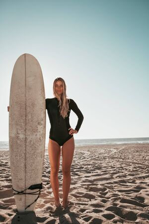 young woman standing with surfboard at Malibu beach. california lifestyle Archivio Fotografico