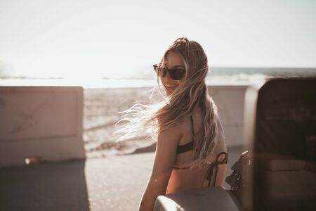 surfer girl standing by a car at the beach. california lifestyle 스톡 콘텐츠
