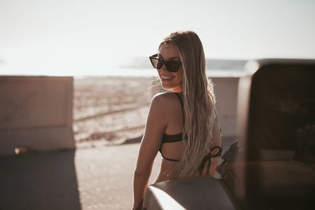 surfer girl standing by a car at the beach. california lifestyle Stock Photo