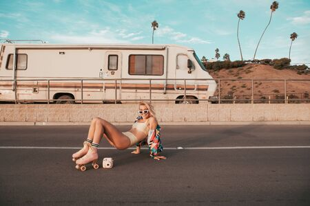 retro style skater girl with a camper van in the background. california lifestyle