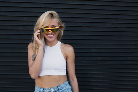 cool young woman standing by a wall with sunglasses.