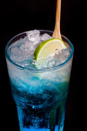 glass of blue cocktail with lime on black background photo