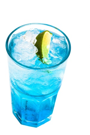 glass of blue cocktail with lime on white background photo