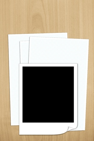 blank photo frame on white paper isolted on wooden background photo