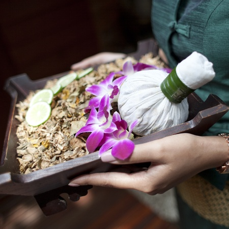 Spa massage setting with thai herbal compress stamps on woman hand