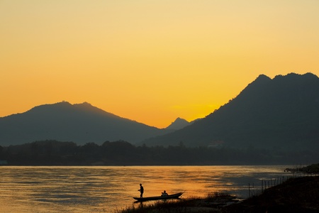 Laos fisherman at river  on sunset  photo