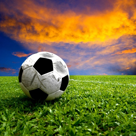 Football, real soccer ball on green grass at sunset photo
